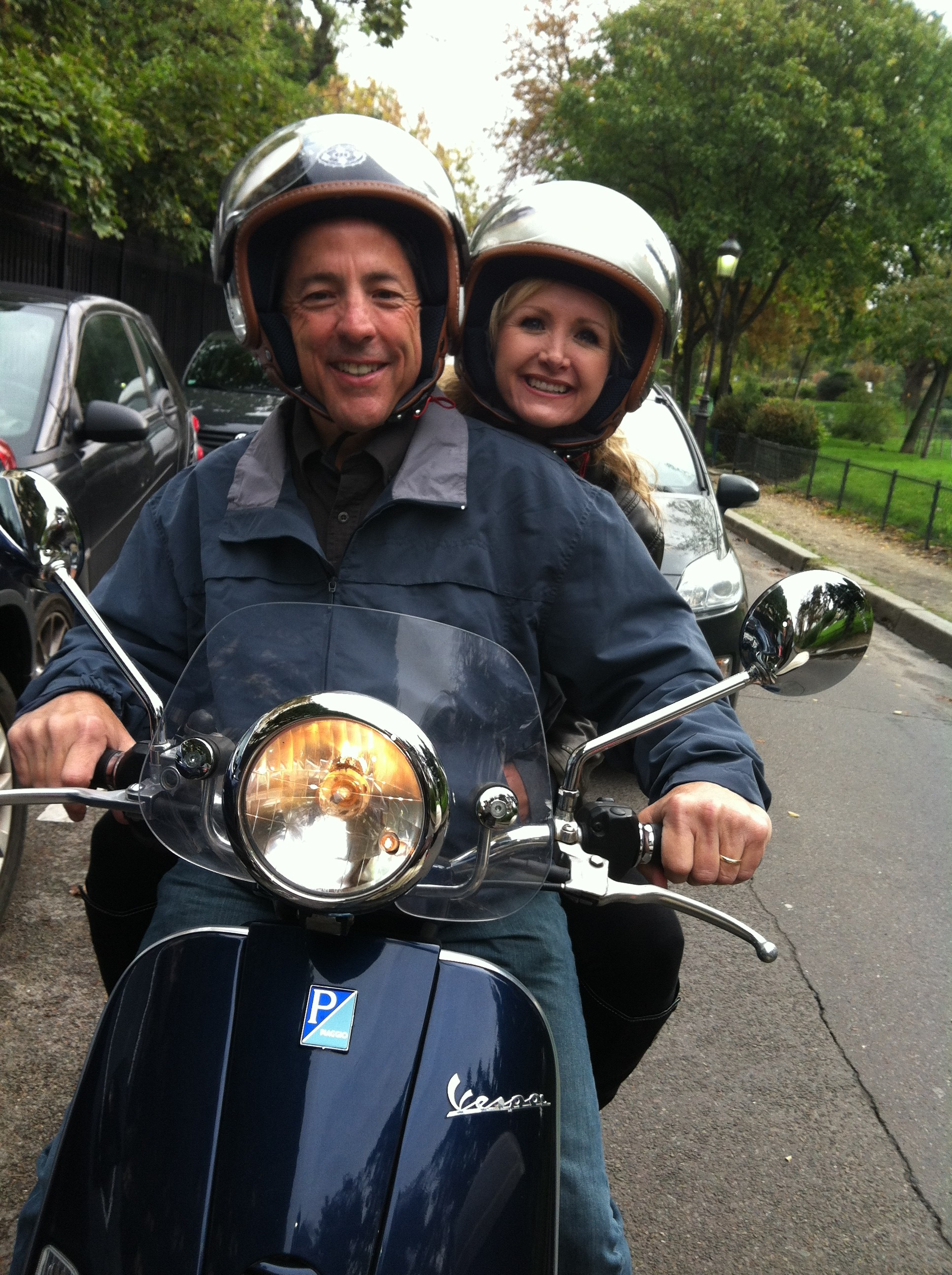 Carrie & Boby at the wheel of a Vespa scooter in the street of Paris France during a Paris sightseeing Tour.